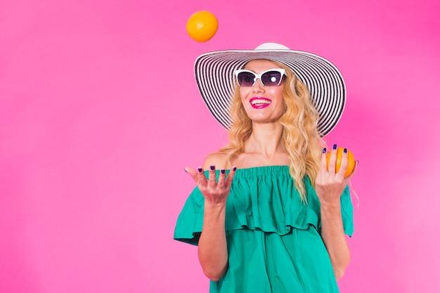 ピンクの壁を楽しんでいるオレンジとサングラスと帽子の美しいスタイリッシュな女性。夏、休日、ファッションのコンセプト。