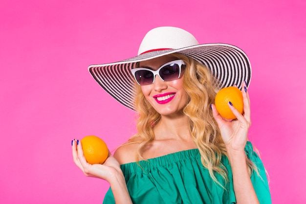 Красивая стильная женщина в солнцезащитных очках и шляпе с апельсинами, развлекаясь над розовой стеной. лето, праздник и концепция моды.