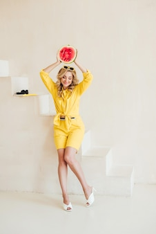 노란색 옷을 입은 아름다운 세련된 여성과 손에 수분이 많은 수박이 있는 여름 선글라스. 행복한 여름, 휴가, 영감. 부드러운 선택적 초점입니다.