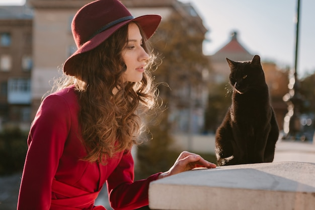 Bella donna alla moda in vestito viola in via della città, tendenza di moda primavera estate autunno stagione indossa il cappello, guardando un gatto