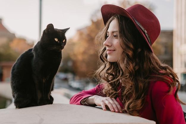 Bella donna alla moda in vestito viola e cappello che cammina nella via della città, tendenza della moda primavera estate autunno stagione, gatto nero
