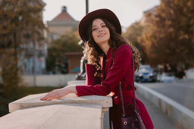 Bella donna alla moda in vestito viola che cammina nella via della città, tendenza di moda primavera estate autunno stagione indossando il cappello, tenendo la borsa