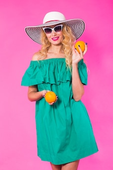 Beautiful stylish woman in sunglasses and hat with oranges having fun over pink background. summer