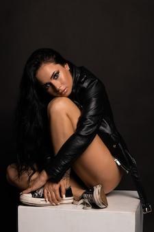 黒革のジャケットを着ている美しいスタイリッシュな女性。長い巻き毛のファッショナブルで自信のある女の子。服、スタイル、ファッション