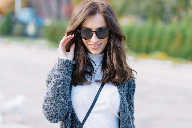 공원의 배경에 카메라를보고 선글라스에 검은 머리를 가진 아름 다운 세련 된 여자