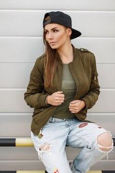 Красивая стильная женщина с веснушками в бейсболке в модной зеленой куртке