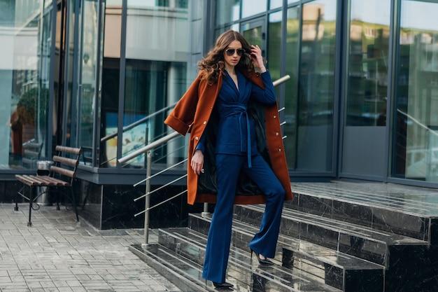 Bella donna alla moda con passeggiate in strada di affari della città urbana vestita di caldo cappotto marrone e abito blu, stile di strada moda alla moda primavera autunno, indossando occhiali da sole