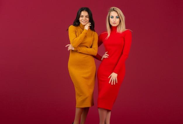 Красивые стильные женщины-друзья в желтых и красных осенне-зимних модных вязаных платьях позирует изолированы на красной стене