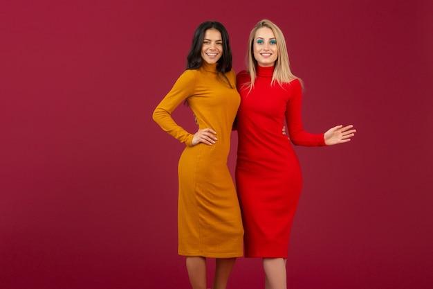 노란색과 빨간색 가을 겨울 패션 니트 드레스에 아름 다운 세련 된 여자 친구는 붉은 벽에 고립 된 포즈