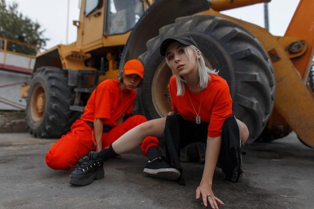 Красивая стильная молодая пара моделей в кепках и желтой одежде позирует возле строительной техники