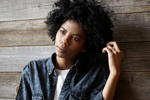 Bella elegante giovane donna dalla pelle scura con taglio di capelli afro seduto al caffè, in attesa di cappuccino, appoggiandosi alla schiena sulla parete di legno, toccando i suoi capelli ricci, avendo uno sguardo pensoso e sognante