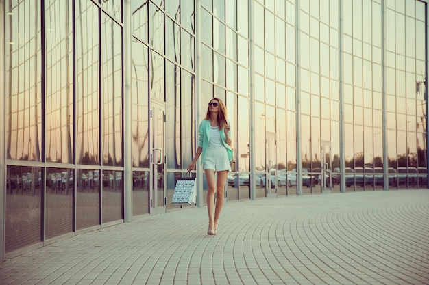 Beautiful stylish young fashion girl in elegant summer clothes, sunglasses and turquoise jacket. lifestyle.