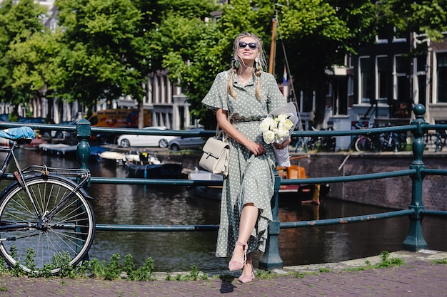 A beautiful stylish young girl standing on the pavement in a fashion pose with a bunch of white flowers in a long green dress and cute flat shoes with ties. street style in amsterdam
