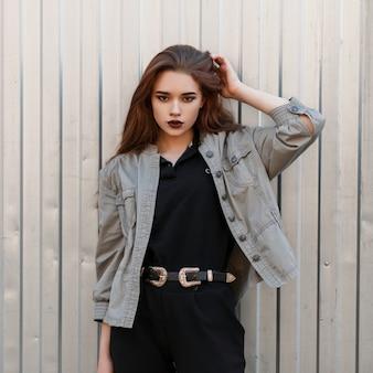 금속 벽 근처 포즈 유행 옷에 아름 다운 세련 된 젊은 모델 여자