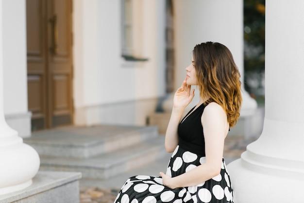 Красивая стильная молодая беременная женщина, держащая руку на животе