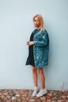 여름 날에 빈티지 벽 근처 운동화에 검은 유행 드레스에 유행 긴 데님 재킷에 아름 다운 세련 된 젊은 여자 금발
