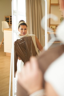 아름 다운 세련 된 젊은 여자 집에서 거울 앞에서 드레스를 선택