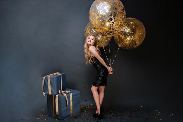 Bella giovane donna alla moda sui tacchi, bionda riccia lunga, vestito di lusso nero con grandi palloncini pieni di orpelli dorati. regali, festa di compleanno, festeggiamenti, sorrisi.