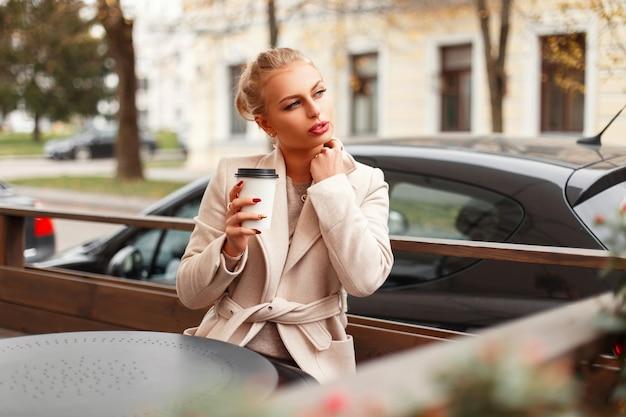 코트에 아름 다운 세련 된 젊은 여자는 카페에 앉아 야외에서 뜨거운 음료를 마신다