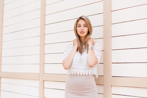 夏の日の木製の壁の近くでポーズをとる華麗なネックレスとベージュのスカートの飾りとヴィンテージのレースのブラウスの美しいスタイリッシュな若い女性