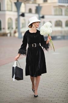 トレンディな帽子を歩いている美しいスタイリッシュな若い女性は、大きな素晴らしい花の香りがします。街の外観で遊歩道を楽しんで笑顔の魅力的なファッショナブルな女性