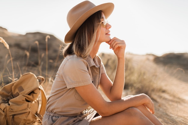 Beautiful stylish young woman in khaki dress in desert sand traveling in africa on safari wearing hat and backpack