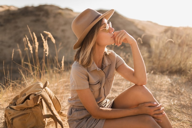 Beautiful stylish young woman in khaki dress in desert traveling in africa on safari wearing hat and backpack on hot summer day