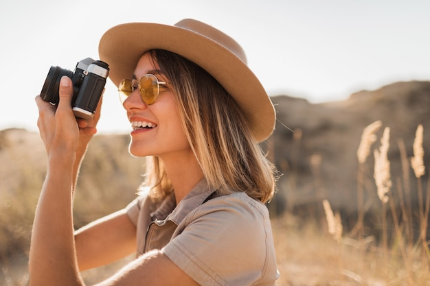Beautiful stylish young woman in khaki dress in desert traveling in africa on safari wearing hat taking photo on vintage camera