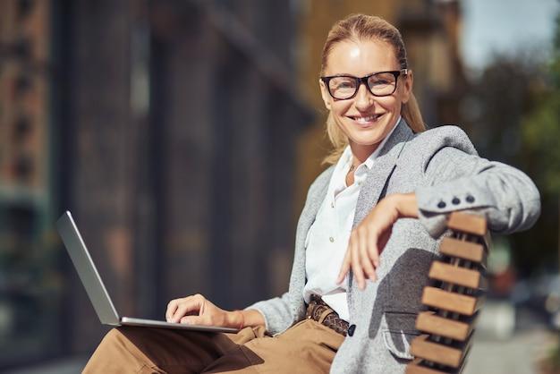 야외 벤치에 앉아 노트북에서 온라인으로 작업 eyeglases를 입고 아름 다운 성공적인 중간 세 비즈니스 여자, 그녀는 카메라를보고 웃