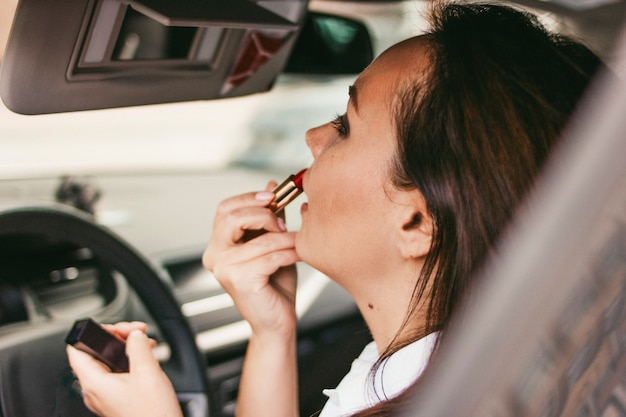 Beautiful successful elegant brunette young woman painting lips with red lipstick in car