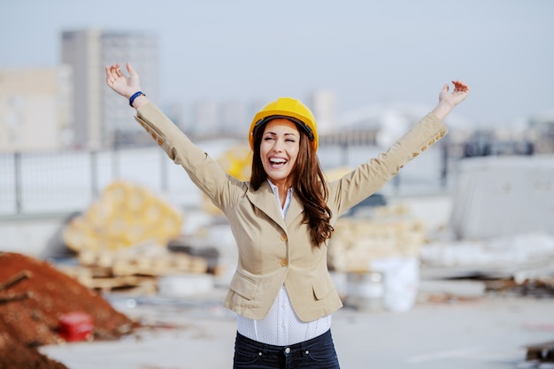 Beautiful successful female architect cheering for excellent done job at construction site.