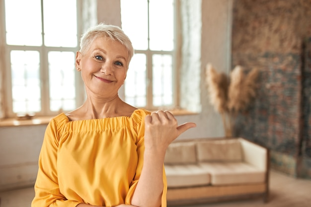 Beautiful successful middle aged female real estate agent with pixie haircut making thumbs up gesture, pointing finger at cozy living room with stylish interior design, offering apartment for sale