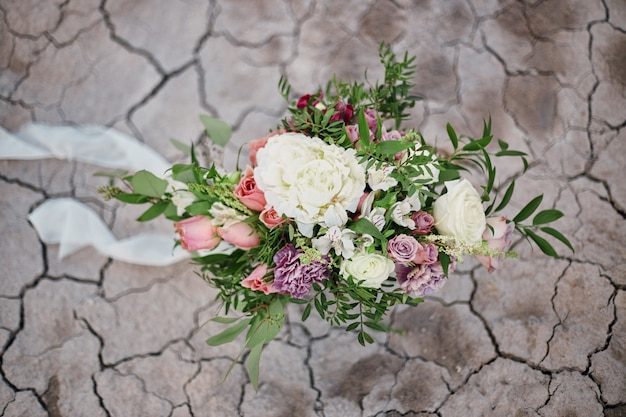 Beautiful summer bouquet of roses on cracked earth