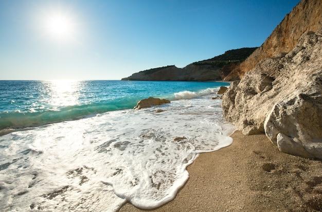 Красивое летнее побережье пляж порто кацики на ионическом море (лефкас, греция) с солнцем в небе и волной