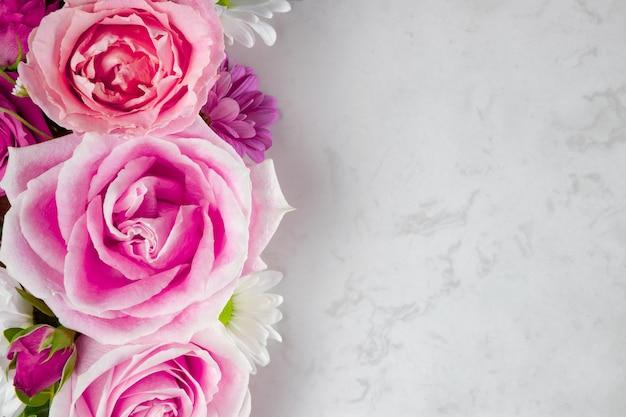 美しい夏の花。ピンクのバラと白いヒナギクのトップ ビュー。