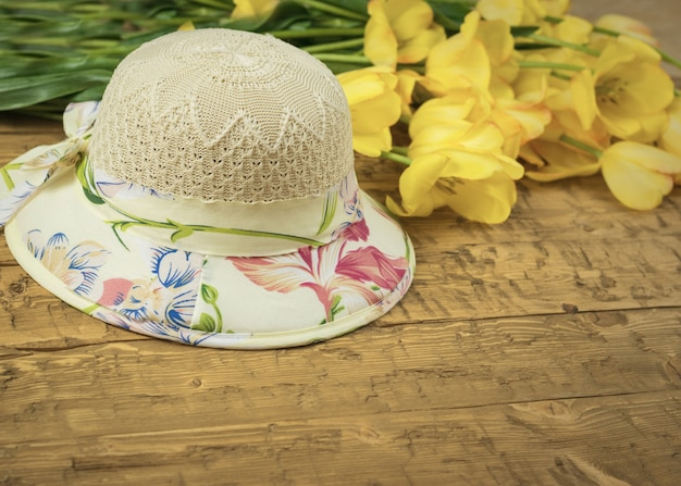 Beautiful summer hat and a bouquet of yellow tulips on a wooden table.