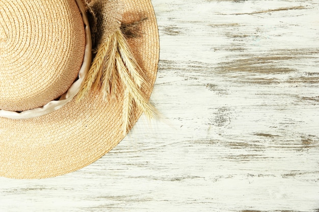 Beautiful summer hat with spikelets on wooden background