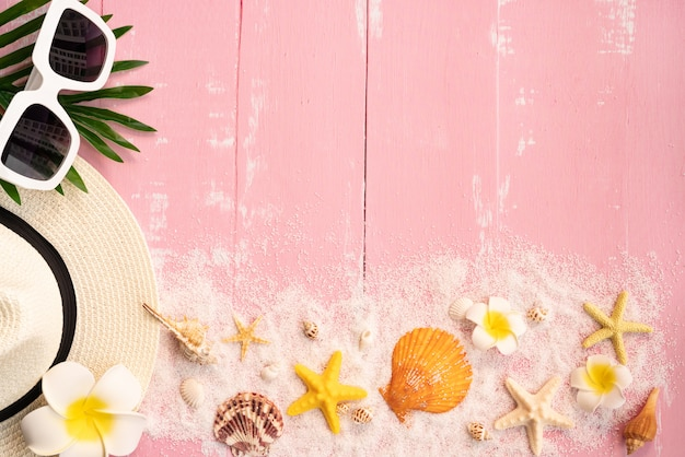 Beautiful summer holiday, beach accessories, seashells, sand, hat, sunglasses and palm leave