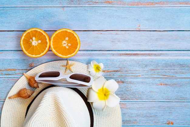 Beautiful summer holiday, beach accessories, sunglasses, hat and orange