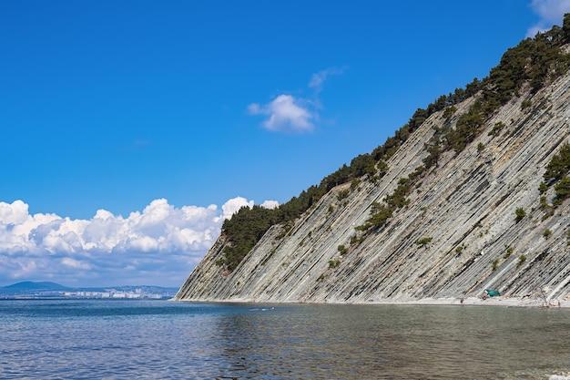 美しい夏の風景、雲のある真っ青な空、木々のある急な崖、野生の石のビーチ。ゲレンジークのリゾート都市。ロシア、黒海沿岸