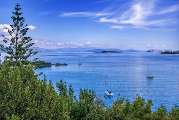 美しい夏の風景–穏やかな海の水面、白いヨット、緑の木々、地平線上の山々。コルフ島、ギリシャ。