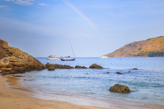 Beautiful summer landscape with rainbow and ships above the sea in the phuket province in thailand.