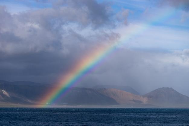 바다, 언덕에 작은 마을, 푸른 하늘, 구름과 수평선에 산에 밝은 화려한 무지개와 아름 다운 여름 풍경입니다. 아이슬란드, 반도.