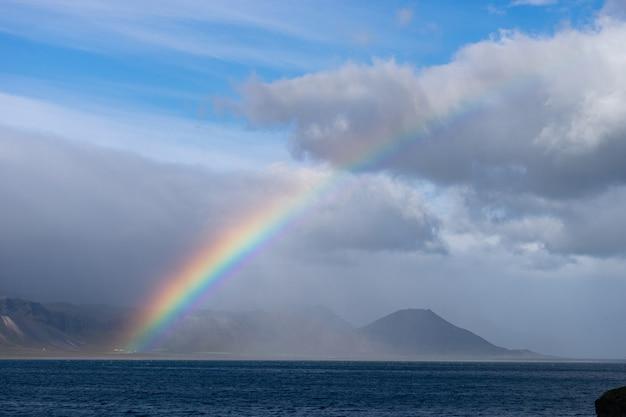 海、丘の上の小さな村、青い空の明るくカラフルな虹、地平線上の雲と山々のある美しい夏の風景