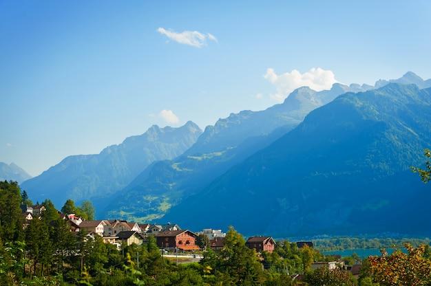 山の近くに小さな家がある美しい夏の風景。スイスアルプスの大きな緑の山の牧草地のある風景