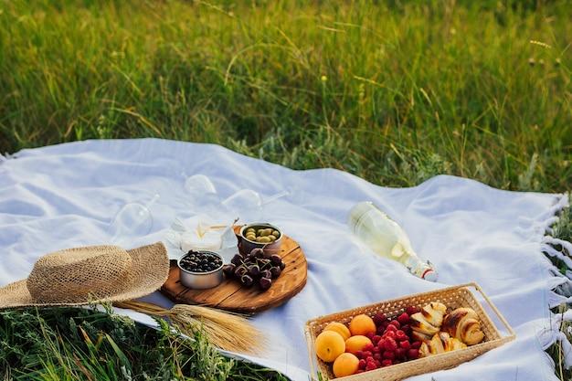緑の丘での美しい夏のピクニック。綿の毛布、麦わら帽子、新鮮な白ワイン、アプリコットをお楽しみください。