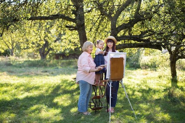 Красивый летний весенний снимок счастливой семьи из трех поколений, маленькой девочки, молодой матери и зрелой бабушки, которые проводят время на открытом воздухе и рисуют картину на мольберте. летний семейный отдых.