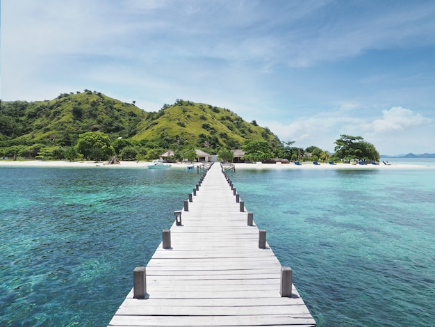 Beautiful summer view of wooden bridge to tropical island.