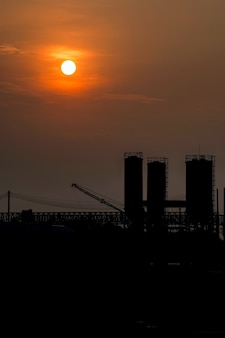 シルエットの産業工場の上の美しい太陽と赤い空。