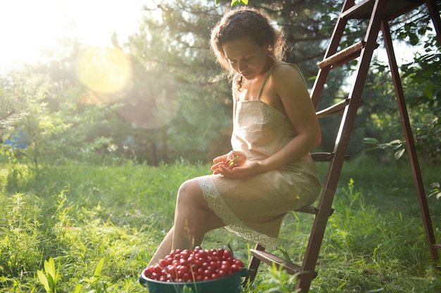 Beautiful sun rays fall into the garden on a summer day while african american ethnicity woman in linen dress sitting on a ladder next to bucket with cherries in orchard.